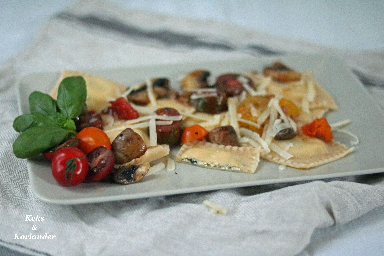 Ravioli mit Ricotta-Basilikum-Füllung und gebratenen Tomaten und Pilzen